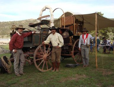 three cowboys standing in front of a wagon at Pioneer Days at Heritage Park